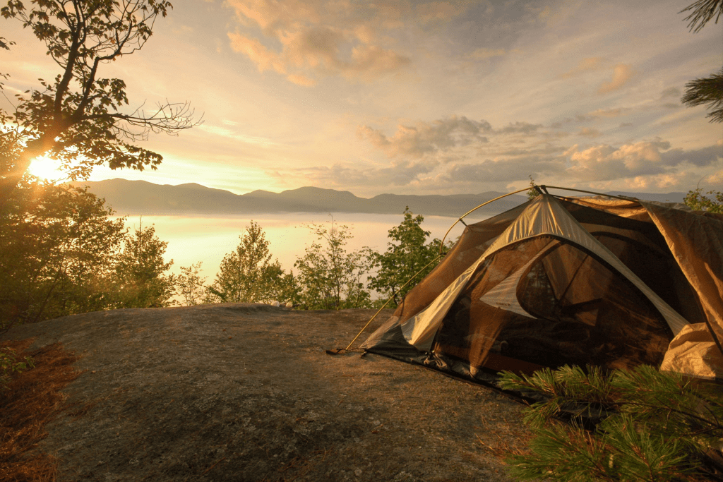 single tent overlooking a scenic lake