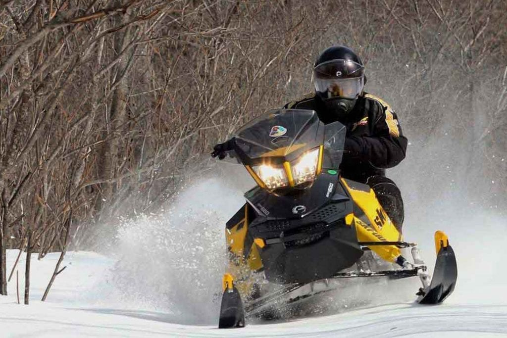 yellow snowmobile kicking up snow